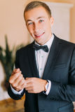Elegant young fashion man in black tuxedo adjusting his cufflinks while looking at the camera indoors Royalty Free Stock Images