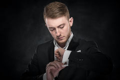 Elegant young fashion man looking at his cufflinks.