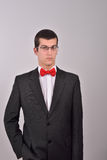 Elegant young fashion man in tuxedo is holding his right hand in Stock Images