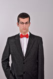 Elegant young fashion man in tuxedo is holding his right hand in Royalty Free Stock Photo