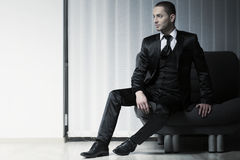 Elegant young fashion man in tuxedo on a sofa,. Blinds background Royalty Free Stock Photography