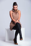 Elegant young fashion woman sitting on a white chair. Holding both hands on her knee Stock Photo