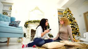 Elegant young female gossip and use smartphone, sit on floor against fireplace and Christmas tree in big living room. Two young women friends chat and smile at stock video