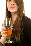 Elegant young female model holding drink looking up Royalty Free Stock Image