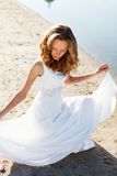 Elegant young girl bride in a white dress on a sandy river beach Stock Photos