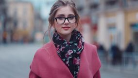 Elegant young girl in a stylish look, walking down the street and looking right towards the camera. Shopping time stock video