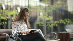 Elegant young girl using the black tablet. Beautiful student in glasses. With a digital tablet sitting in the open space. Business woman with a tab looks around stock footage