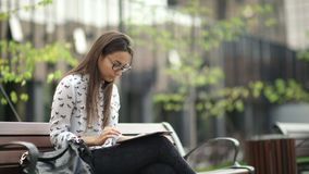 Elegant young girl using the black tablet. Beautiful student in glasses. With a digital tablet sitting in the open space. Young woman with a tab looks around stock video