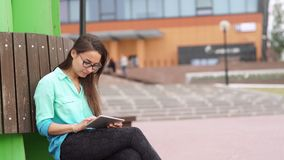 Elegant young girl using the mini-tablet. Beautiful student in glasses with a digital tablet sitting in the open space. Business woman with a tab looks around stock video