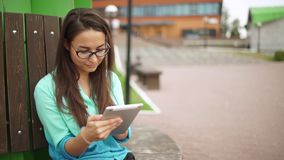 Elegant young girl using the mini-tablet. Beautiful student in glasses. With a digital tablet sitting in the open space. Business woman with a tab looks around stock footage