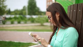 Elegant young girl using the mini-tablet. Beautiful student in glasses. With a digital tablet sitting in the open space. Business woman with a tab looks around stock video footage