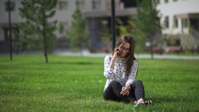 Elegant young girl using the tablet. Beautiful student in glasses. With a digital tablet sitting on the grass. She takes a tablet in hands. Youth using gadgets stock video