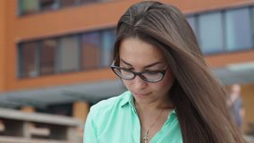 Elegant young girl using the tablet. Young woman with a tab. Elegant young girl using the tablet. Beautiful student in glasses with a digital tablet sitting in stock video