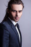 Elegant young handsome long-haired man in costume. royalty free stock image