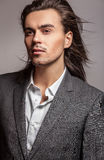 Elegant young handsome long-haired man in costume. Royalty Free Stock Photography