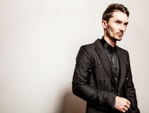 Elegant young handsome man in black costume. Studio fashion portrait. Royalty Free Stock Photos