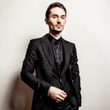 Elegant young handsome man in black costume. Studio fashion portrait. Royalty Free Stock Photography