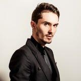 Elegant young handsome man in black costume. Studio fashion portrait. Stock Image