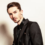 Elegant young handsome man in black costume. Studio fashion portrait. Stock Photography