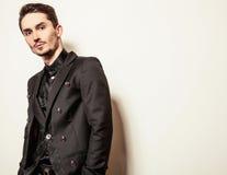 Elegant young handsome man in black costume. Studio fashion portrait. Stock Photo