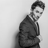Elegant young handsome man in black costume. Studio fashion portrait. Royalty Free Stock Image