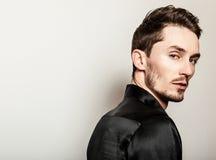 Elegant young handsome man in black silk shirt. Studio fashion portrait. Elegant young handsome man in black silk shirt royalty free stock photography