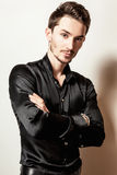 Elegant young handsome man in black silk shirt. Studio fashion portrait. Royalty Free Stock Photography