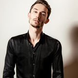Elegant young handsome man in black silk shirt. Studio fashion portrait. Royalty Free Stock Images