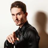 Elegant young handsome man in black silk shirt. Studio fashion portrait. Stock Photo