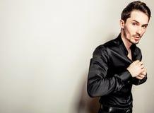Elegant young handsome man in black silk shirt. Studio fashion portrait. Royalty Free Stock Photo