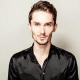 Elegant young handsome man in black silk shirt. Studio fashion portrait. Stock Photography
