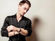 Elegant young handsome man in black silk shirt. Studio fashion portrait. Royalty Free Stock Images