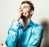Elegant young handsome man in blue silk shirt. Studio fashion portrait. Royalty Free Stock Photography