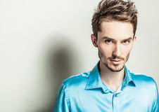 Elegant young handsome man in blue silk shirt. Studio fashion portrait. Royalty Free Stock Images