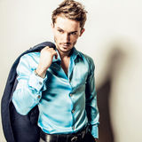 Elegant young handsome man in blue silk shirt. Studio fashion portrait. Royalty Free Stock Photo