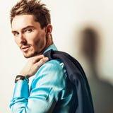 Elegant young handsome man in blue silk shirt. Studio fashion portrait. Stock Image