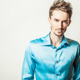 Elegant young handsome man in blue silk shirt. Studio fashion portrait. Royalty Free Stock Image