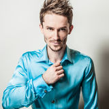 Elegant young handsome man in blue silk shirt. Studio fashion portrait. Stock Image