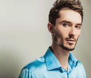 Elegant young handsome man in blue silk shirt. Studio fashion portrait. Stock Photos