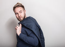Elegant young handsome man in dark blue classic shirt and jacket on his shoulder. Studio fashion portrait royalty free stock photos