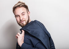 Elegant young handsome man in dark blue classic shirt and jacket on his shoulder. Studio fashion portrait royalty free stock images