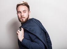 Elegant young handsome man in dark blue classic shirt and jacket on his shoulder. Studio fashion portrait stock photography