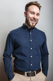 Elegant young handsome man in dark blue classic shirt. Studio fashion portrait. Stock Images