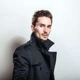 Elegant young handsome man in long stylish dark blue coat. Studio fashion portrait Stock Images