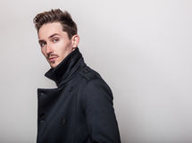 Elegant young handsome man in long stylish dark blue coat. Studio fashion portrait Royalty Free Stock Photography