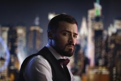 Man in Suit at Night. Elegant young handsome man over night city background. Portrait of guy looking at the camera stock photo