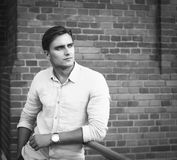 Elegant young handsome man posing over brick wall. Fashion portrait Royalty Free Stock Photography