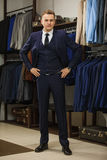 Elegant young handsome man. A young stylish man in a black cloth jacket. It is in the showroom, trying on clothes, posing. Adverti Royalty Free Stock Images
