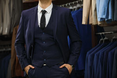 Elegant young handsome man. A young stylish man in a black cloth jacket. It is in the showroom, trying on clothes, posing. Adverti Stock Photo