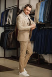 Elegant young handsome man. A young stylish man in a blue cloth jacket. It is in the showroom, trying on clothes, posing. Advertis Royalty Free Stock Photography